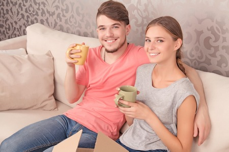 spouses: Warm atmosphere at home. Upbeat happy couple sitting on the couch and holding cups while  drinking tea