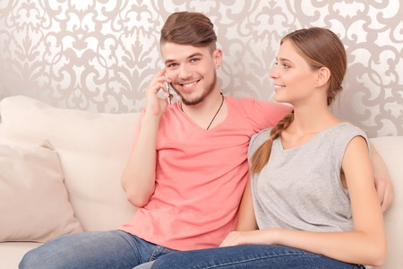 elated: Brisk conversation. Pleasant elated  young husband sitting with his wife on the couch and holding mobile phone while talking