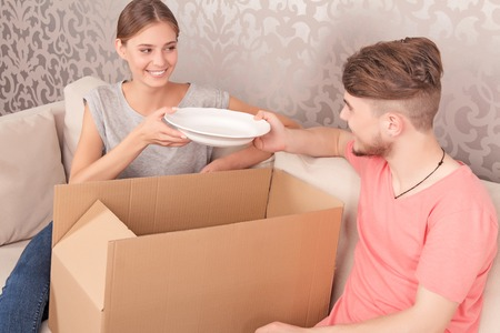 coziness: Making coziness. Pleasant  upbeat young couple sitting on the sofa and holding plate while unpacking box.