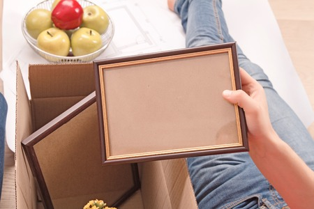 revel: Revel in family photos.Close up of pleasant young husband holding frame while unpacking boxes.