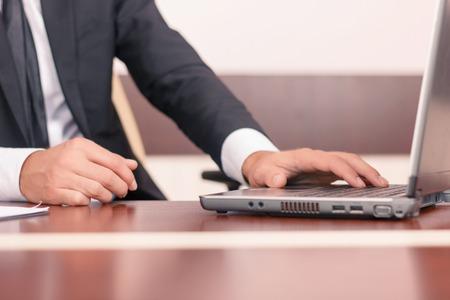 diligente: Abogado de bienes. Cerca de la computadora portátil abierta de pie sobre la mesa y ser utilizado por trabajador diligente