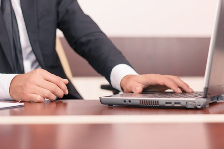 diligent: Real lawyer. Close up of opened laptop standing on the table and being used by diligent worker Stock Photo
