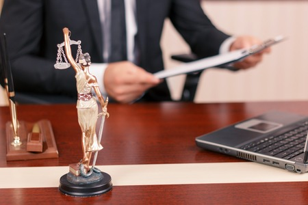 Law and equility. True lawyer sitting at the table and holding papers with statue of justice on forefront Stock Photo