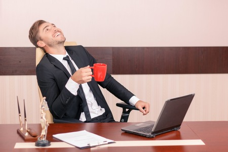 upbeat: Time to relax. Upbeat handsome lawyer sitting at the table and drinking tea while having rest Stock Photo