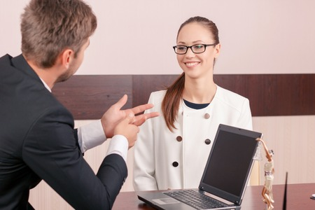 vivacious: Involved in communication.  Vivacious positive woman sitting at the table and smiling while having conversation with professional lawyer. Stock Photo