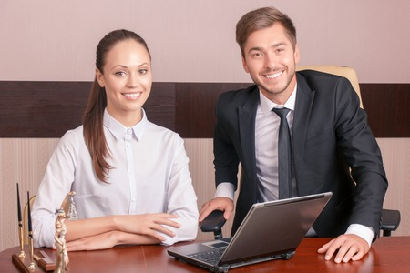 female lawyer: Real lawyers. Nice smiling colleagues sitting at the table and feeling happy while working together. Stock Photo
