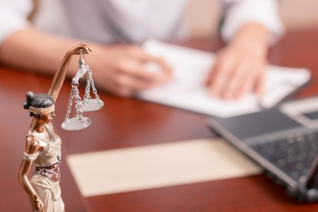 justice: Follow the law. Professional lawyer sitting at the table and signing papers with justice statue standing on surface in forefront. Stock Photo