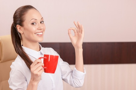 upbeat: Life is a great thing. Upbeat smiling young woman holding cup of coffee and drinking it while evincing positivity. Stock Photo