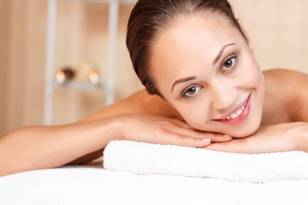 salon de belleza: Feliz de estar aqui. Agradable atractiva joven cruzando los brazos y sonriendo mientras está acostado en el sofá en salón de belleza Foto de archivo