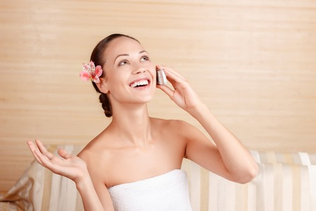 brisk: Brisk conversation. Pleasant smiling woman holding mobile phone and having conversation on it while rejoicing in spa