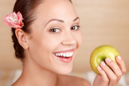 safe and sound: Safe and sound. Beautiful vivacious lade smiling and holding apple while visiting spa salon