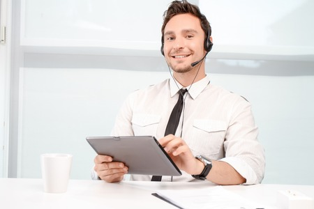 working hours: Love my job. Pleasant smiling  call center operator sitting at the table and holding laptop while having working hours.