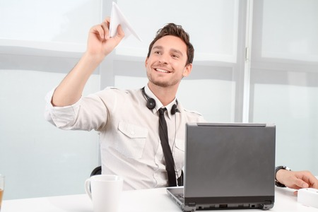 plane table: Time for fun. Pleased lively call center operator holding paper plane and sitting at the table while relaxing Stock Photo