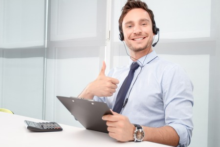 over the moon: Life is good. Vivacious euphoric call center operator sitting at the table and thumbing up while feeling over moon.