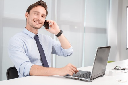 important phone call: Important call. Nice positive young call center operator holding mobile phone and working on computer while doing his job. Stock Photo