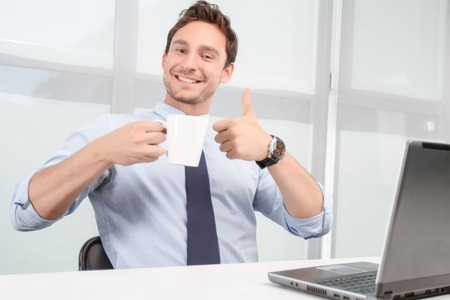 upbeat: Revel in positivity. Nice upbeat call center operator thumbing up and drinking tea while evincing joy. Stock Photo
