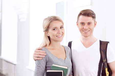 eagerness: Full of eagerness to study.  Pleasant delighted students holding books and  bonding to each other while expressing joy Stock Photo