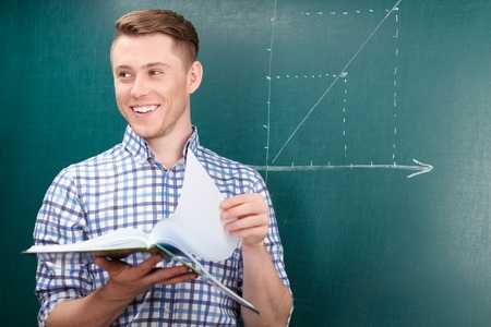 to be pleasant: Want be a real professional. Pleasant diligent student holding book and doing task while standing near  blackboard Stock Photo