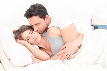 expressing: Forever mine. Pleasant young couple lying in bed and embracing while expressing love Stock Photo