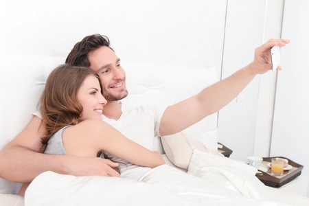 nice guy: Lets smile. Nice smiling young couple bonding to each othe rand making selfie while lying in bed
