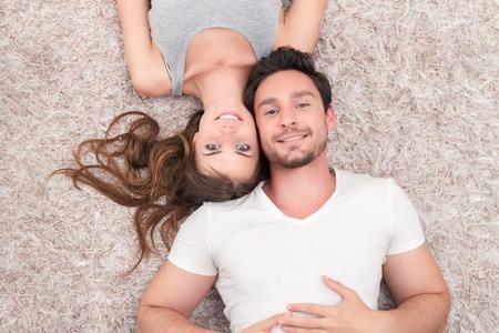 Happy together. Positive young couple smiling and lying on the floor while spending time together. Standard-Bild