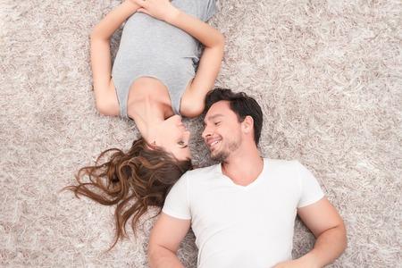 couple sleeping: Todos los días juntos. Vista superior de la joven pareja positivo sonriendo y mirando el uno al otro mientras está acostado en la alfombra.
