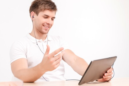 gesticulating: Portrait of a handsome smiling young man sitting at the table holding a tablet in his hands wearing earphones, gesticulating while talking with his partner on videoconference