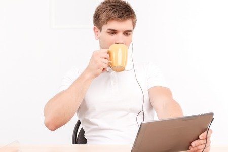 talk big: Portrait of a handsome young man sitting at the table holding a tablet in his hands wearing earphones, drinking coffee from big cup while listening to his partner on skype talk Stock Photo