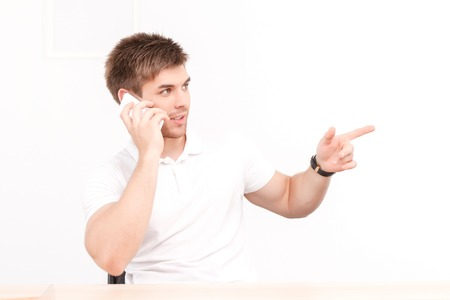 telephone interview: Portrait of a young handsome manager sitting in the office, talking on the phone gesticulating while discussing some business matters, looking serious