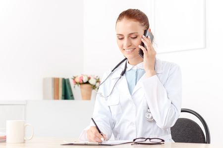 doctors smiling: Nice conversation. Contented overjoyed woman doctor writing and talking on mobile phone while sitting at the table Stock Photo