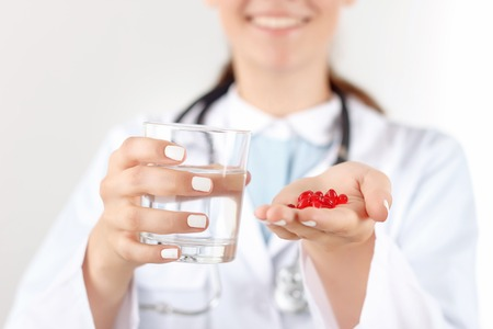 doctor giving glass: Here you are. Pleasant smiling woman doctor holding glass of water and pills while giving them to her patient