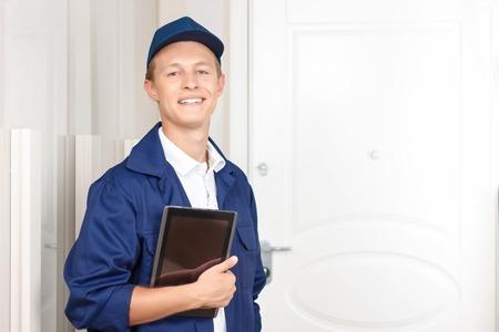 diligente: trabajador diligente. Niza repartidor vivaz celebraci�n de ordenador port�til y esperando cerca de la puerta mientras que la entrega de paquetes.