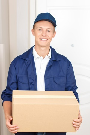 upbeat: Best service. Positive upbeat deliverymen waiting near the door and holding box while delivering it Stock Photo