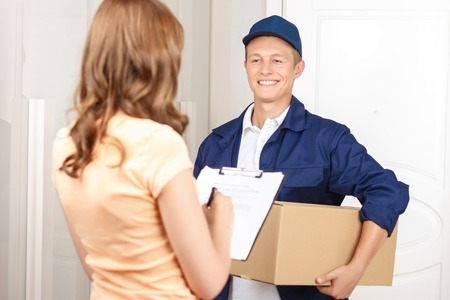 hilarious: Working for your comfort. Nice hilarious deliveryman holding parcel and expressing positivity while giving it to client Stock Photo