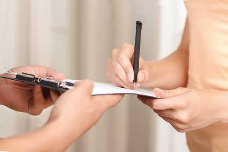 storekeeper: Just sign it. Close up of pleasant client signing paper and giving it to deliveryman while receiving parcel