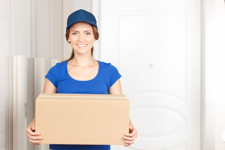 upbeat: Working for your comfort. Nice lovely upbeat deliverywoman holding parcel and expressing positivity while standing near door