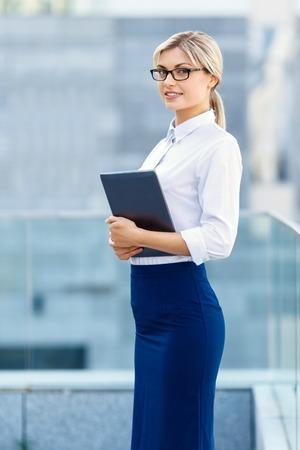 diligente: Buen trabajo. Alegre diligente joven mujer de negocios la celebraci�n de ordenador port�til y de pie cerca de edificio de oficinas, mientras deleit�ndose con positividad.