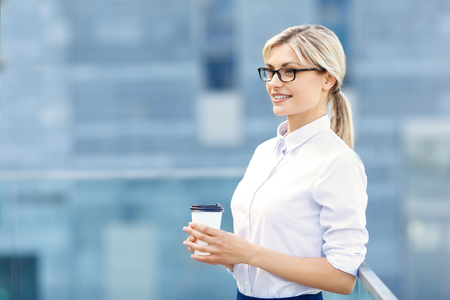 take it easy: Take it easy. Pleasant smiling business woman drinking coffee and looking aside while having rest. Stock Photo