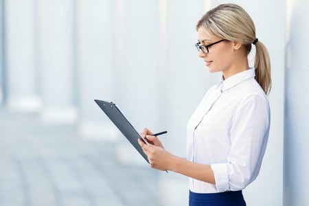 resolved: Time to show results. Resolved hardworking businesswoman holding folder and writing while standing near columns Stock Photo