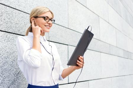 스트레스를 줄이는 가장 좋은 방법. 노트북을 들고 음악을 듣고 계시하는 동안 헤드폰을 착용하고 행복하게 낙관적 인 사업가 스톡 콘텐츠