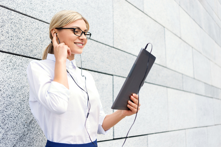 upbeat: Best way to reduce stress. Blissful upbeat businesswoman holding laptop and wearing headphones while reveling in listening to music Stock Photo