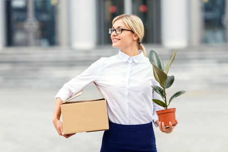laugher: Ready to work. Pleasant vivacious businesswoman holding box and flower pot while going to work