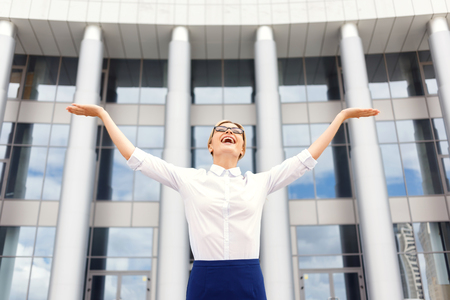 feeling up: Feeling good everyday.  Overjoyed  beautiful businesswoman holding her hands up and feeling over the moon while standing near office building