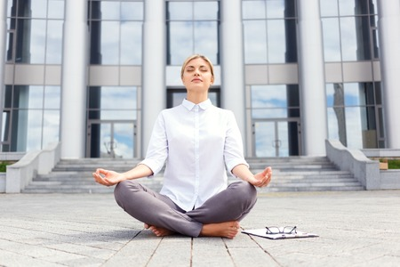 laugher: In harmony with mid. Pleasant beautiful young businesswoman sitting on the ground near office building and practicing yoga while feeling delighted Stock Photo