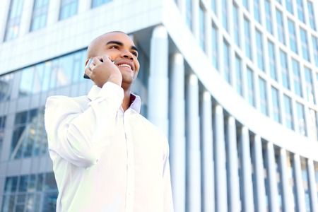 brisk: Nice conversation. Handsome smiling upbeat businessman holding  mobile phone and looking aside while having brisk talk. Stock Photo