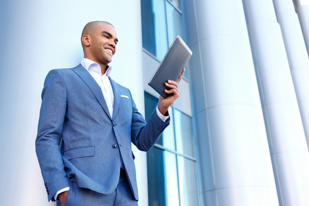 upbeat: In pace of time. Blissful upbeat handsome businessman holding laptop and standing near column while evincing joy Stock Photo