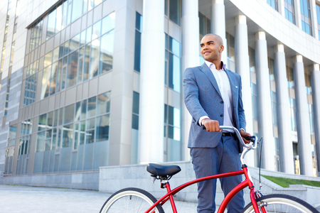 elated: Time to ride. Lively elated handsome businessman holding bicycle and looking aside while going to ride. Stock Photo