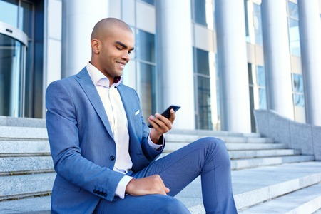 upbeat: Time to rest. Handsome smiling upbeat businessman sitting on the stairs and holding mobile pone while typing message.