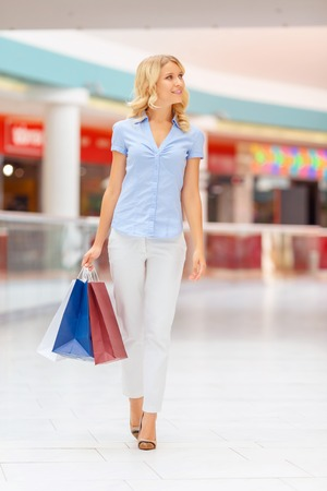 blissful: It is a nice day. Charming blissful young woman holding packages and relaxing in shopping mall while evincing joy