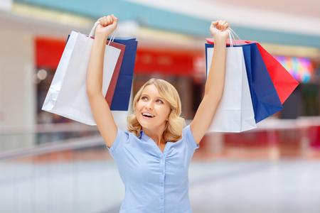 blissful: Feel happiness. Pleasant blissful young woman keeping her hands up and holding  packages while shopping Stock Photo